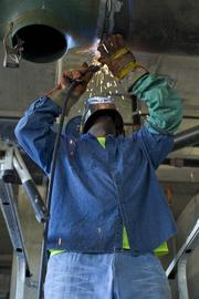 Harold Boyd of Bruner Corp. welds a water pipe on the 10th floor.