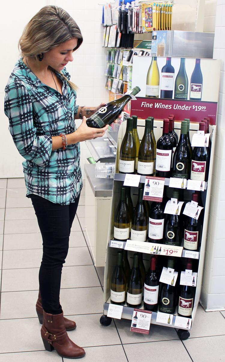 Emily Roff of Dallas checks out the new line-up of wines at a 7-Eleven store.