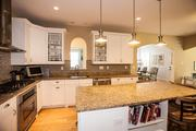 Oak Tree: The kitchen has stainless steel appliances with a gas cooktop, double ovens and a large center island.