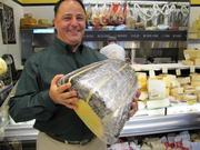 Bill Mignucci with a slab of provolone —part of a cache of 5,000 pounds of cheese brought in for the Di Bruno Bros. opening at Franklin House.