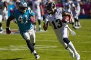 St. Louis Rams wide receiver Chris Givens tries to run away from Carolina Panthers defensive back Captain Munnerlyn after making a catch.