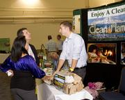 Attendees of the SARTA CleanStart/AgStart Showcase learn about the product Clean Flame at the exhibit hall.