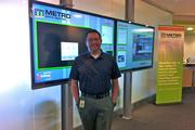 With a display in the shared lobby of DEC and Metro Data Center, Jason Ault gains both a client and a product demonstration of the digital displays set up by his company, Coffman Media LLC.