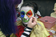 Clown Hanna Beazely gets her face painted by makeup artist Kelly Moore.