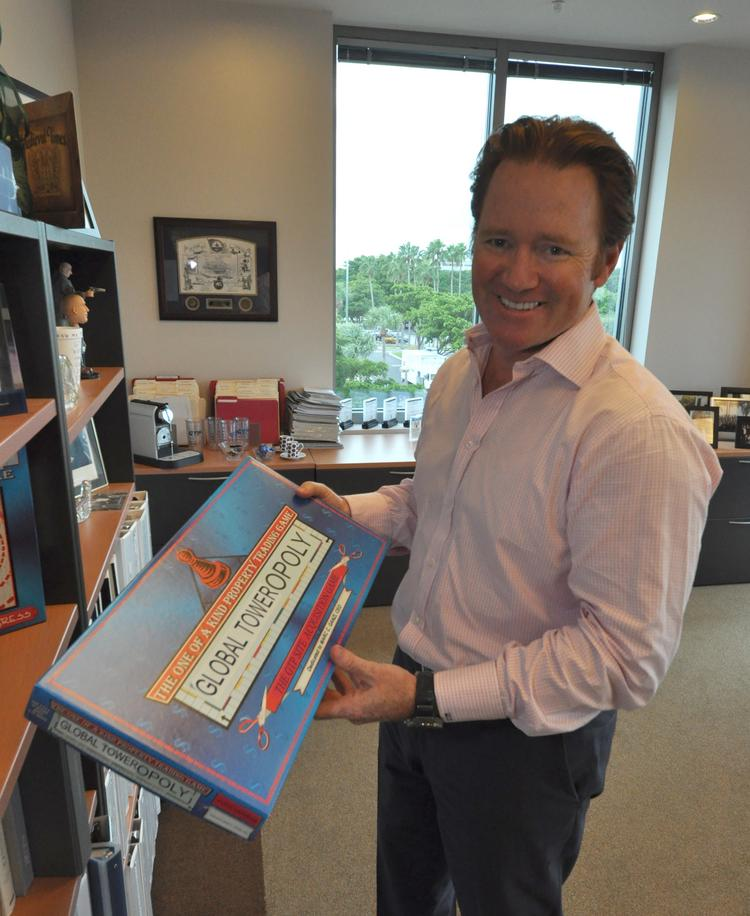 Global Tower Partners CEO Marc Ganzi with the Global Toweropoly game his employees made.