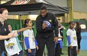 Jags offensive lineman Will Rackley holds a football during a football/cheerleader coaching clinic.