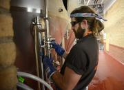 Brewer Chad Hilgenberg cleans a brew tank.