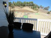 The view from this rear deck shows construction crews working on future home sites in Orinda Grove.
