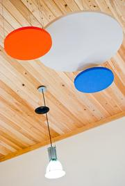 Hardwood flooring was installed on the ceiling, which includes these acoustical clouds with the colors of the company's logo.