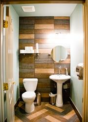 The bathroom continues the wood floor paneling along the wall.