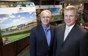 Pinnacle Entertainment CEO Anthony Sanfilippo, left, and River Downs general manager Kevin Kaufman, stand in front of renderings of the new facility that will replace the old River Downs track and grandstand.