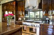 The 20- by 30-foot kitchen has a custom Walnut Burl finish on the cabinets.
