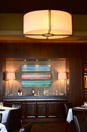 A bar and artwork at the opposite wall of the private dining room