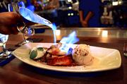 The Bananas Foster sauce is poured in a flash of blue flame. Shiny objects and sugar — awesome way to end any meal.