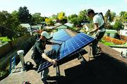 Josh Ford, lead installer and co-owner of Namaste Solar Electric Inc., with installer Kevin Gillette, placing solar panels on a house in Denver.