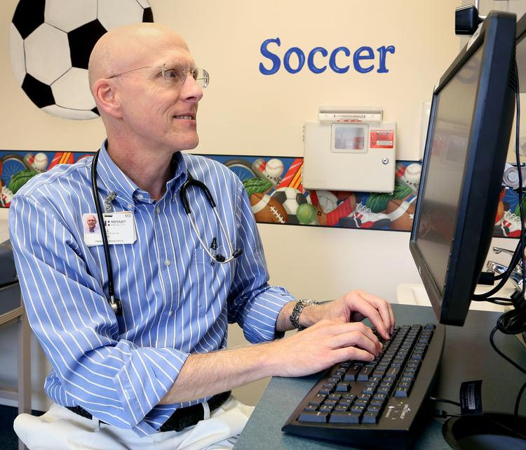 Dr. William Satterwhite at Novant Health Twin City Pediatrics, videoconferences with a patient using a system recently rolled out by Novant.