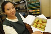 Pia Laza, sales clerk for Liliha Bakery, shows a box of green tea puffs prepared for a customer.