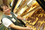Sales clerk Feli Fronda adds a fresh batch of chocolate eclairs to the pastry  display at Liliha Bakery.