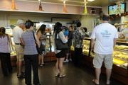 Customers browse the pastries on display at Liliha Bakery.