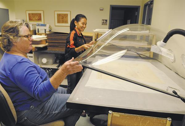 Librarian Lynn Davis, left, and graduate student Mary-Joy Llaguno place an Ossipoff drawing of the Liljestrand House in a humidification chamber for flattening and preservation.