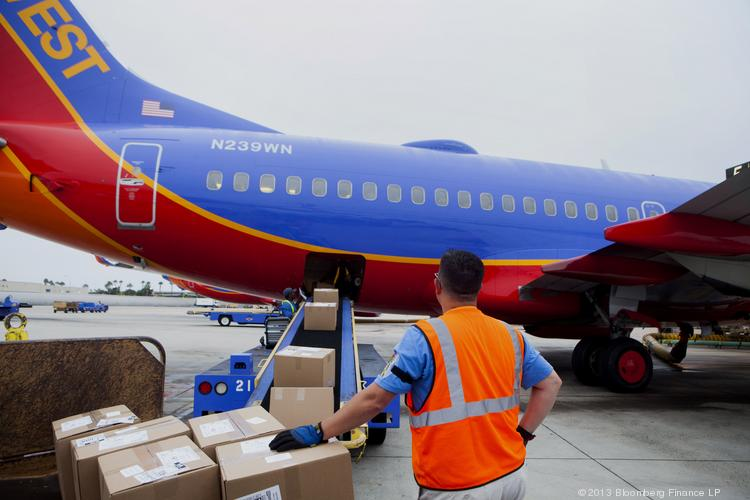 A ground crew member loads cargo onto a Southwest Airlines Co. Boeing Co. 737-7H4 airplane. The airline is adding another nonstop flight in Memphis next summer.