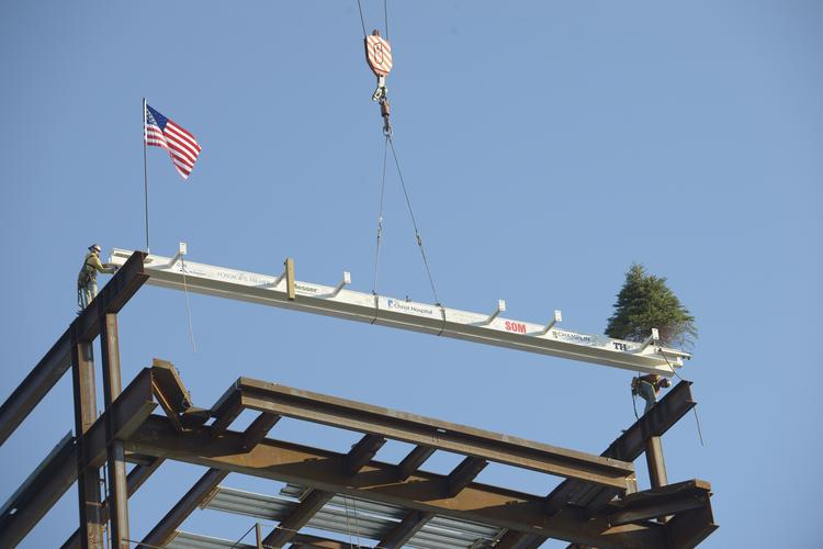 Steelworkers Donovan Pennington, left, and Eddie Franklin, right, place the final beam at the Christ Hospital Joint and Spine Center.