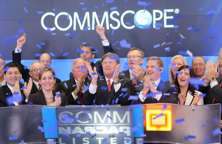 CommScope CEO Eddie Edwards, center with red tie, celebrates its initial public offering and first stock trading today in New York.