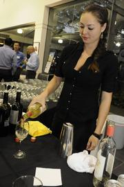 Amber Poling of Memoirs pours a drink during a reception honoring the physicians named to the Best Doctors 2014 Hawaii list published in Friday's print edition of Pacific Business News.