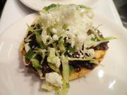 Curried dusted tostada with chorizo black beans