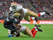 Will Ta'ufo'ou of the Jaguars is stopped by the flying Patrick Willis of the 49ers.