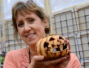 Catherine Galgano of River Mud Handcrafted Pottery poses with one of her Halloween creations.