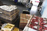 Joe Young, vice president at Chris Produce Co., moves pallets of fresh fruits and vegetables that have just been delivered.