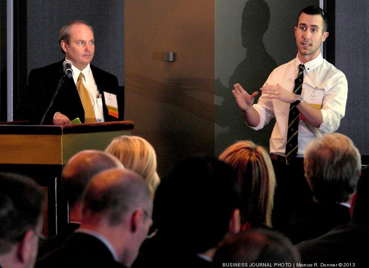 From left, Brad Vancour, of the Zino Society, listens as Zach Parker, Community Organizer/Marketing Director for Snazz.it makes a presentation to Zino Society investors at an event at the Columbia Tower Club.
