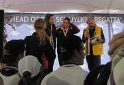 Members of the USRowing women's  team, captained by Kerry Simmonds, at the winner's podium with race volunteer Tony Schneider (in yellow vest).