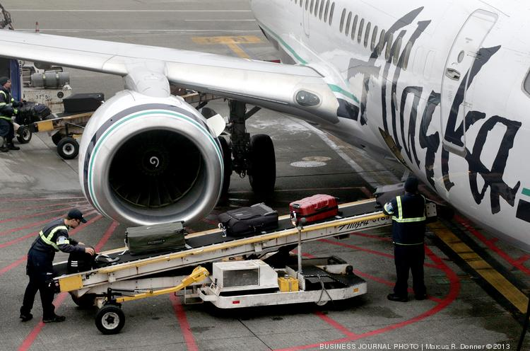 Baggage handlers from Menzies Aviation unload luggage from an Alaska Airlines plane at Seattle-Tacoma International Airport. A ballot measure in the city of SeaTac would raise the minimum wage for many airport workers to $15 an hour.