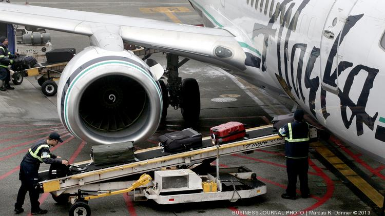 Baggage handlers from Menzies unload Aviation luggage from an Alaska Airlines plane at Sea-Tac airport.