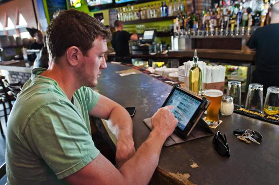 A customer at the Rocky's Sub Pub restaurant in Jeffersonville checked out the beer options on one of Rocky's tablet computers.