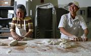 From left, Thuy Huynh, a baker, and Phuong Bui, head baker, at Macrina Bakery work with bread dough.