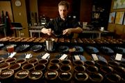 Lennon Fediw, a green coffee quality technician, removes brewed coffee grounds from coffee samples in the tasting room at Starbucks' headquarters building in Sodo.