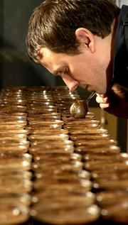 "Banks Thomas, green coffee quality specialist, Starbucks Corp., checks the aroma of freshly brewed lots of coffee in the tasting room at Starbucks headquarters in Sodo. On average, each set of six cups represents a sample from a 40,000-pound lot of green coffee. Thomas moved to Seattle 10 months ago from Vancouver, British Columbia. ""Sodo is a little industrial but with a smattering of cool restaurants and things you can't find anywhere else. It looks like there are some cool things starting to happen in Sodo. It looks like it is becoming a cool part of town."" Banks Thomas Starbucks Corp."