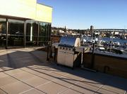 Overlooking Lake Union in Seattle, a huge rooftop expanse tops the new headquarters of the Jeff and Tricia Raikes Foundation headquarters, with a new barbecue awaiting use.