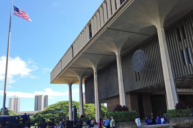 People are seen outside the Hawaii state Capitol in Honolulu Monday as the Legislature convened a special session to consider a bill that would legalize same-sex marriage.