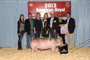 The winners of the Grand Champion Hog, including Dana Foote, David Fowler, Steve Frye, Brant Laue, Greg & Liz Maday, John & Kate Mitchell, Rick Norden, Cynthia Savage, Brad Sprong, Charlie & Tracy Tetrick, Chandler & Tim Thayer, and representatives of KPMG LLP and Laue Ranch, pose with the hog, which they paid a record $40,000 to acquire at the American Royal's Junior Premium Livestock Auction.