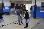 Washington Capitals alumnus Alan May instructs a St. Mary's school student on stickhandling during a Hockey School assembly on Oct. 23.