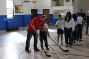 Washington Capitals alumnus Ken Sabourin assists a student.