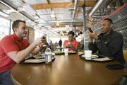 Workers take a break and eat lunch. Why chat when you can text each other?