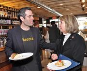 Vic Christopher, co-owner of The Grocery, talks to Rensselaer County Executive Kathy Jimino at the store in downtown Troy, NY. A link of sausages (instead of the customary red ribbon) was cut to mark the store's grand opening Oct. 29.