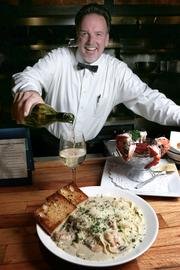 Bob Guettler, a 20-year veteran waiter at 13 Coins, pours a glass of white wine to go with a plate of Venetia (a prawn, scallop and mushroom fettuccine) and a jumbo tiger prawn cocktail.
