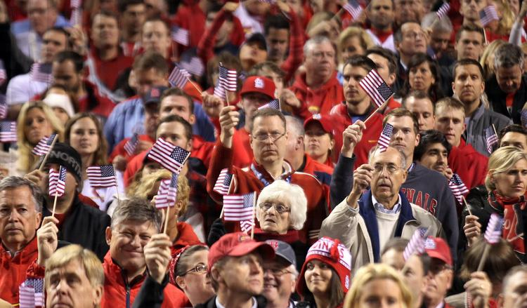 "Baseball fans wave American flags during the singing of ""God Bless America"" during the seventh inning of Game 5 of the World Series at Busch Stadium in St. Louis on October 28, 2013.    UPI/Bill Greenblatt"