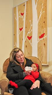 Karen Montgomery and her daughter, Sophie Jones. Eco Baby Daycare owner Robyn Scotland made the background wall hanging in warm, neutral colors.